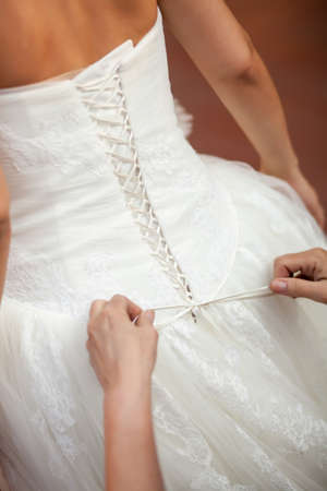 Bridesmaid helping the bride to put her wedding dress on  Tying bow on wedding dress photo
