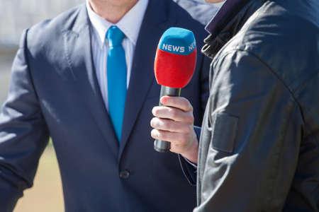 マイクのインタビューを用いるニュース ジャーナリスト