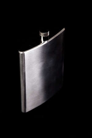 hip flask: Stainless hip flask coming out of dark Stock Photo