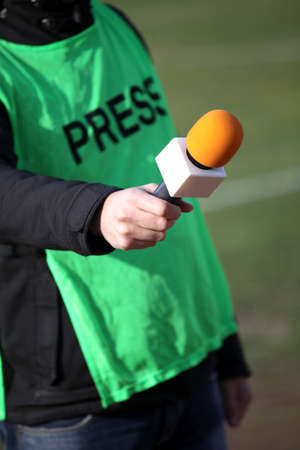 belonging to the caucasoid race: reporter holding microphone for interview during a football mach