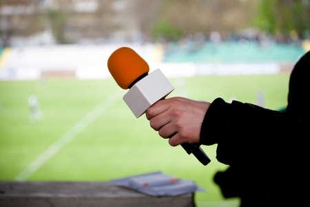 reportero: micrófono asimiento de la mano para una entrevista durante un partido de fútbol
