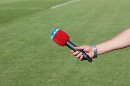hand holding microphone for interview during a football mach Фото со стока