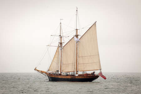 Old ship with white sales, sailing in the sea