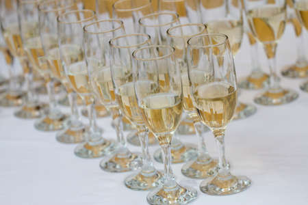 lot of glasses filled with champagne on the party table
