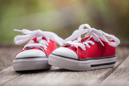 Red baby sneakers on wooden background photo