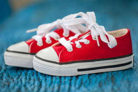 Red baby sneakers on wooden blue background photo