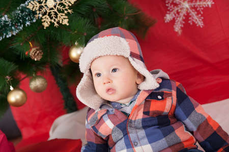 cute baby boy under christmas tree photo