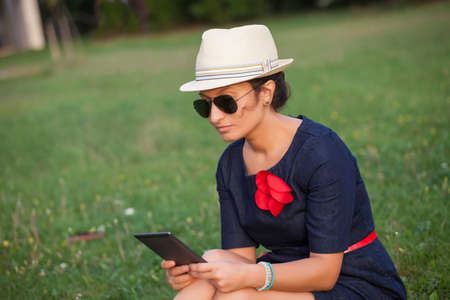 beautiful woman reading e-book in the park photo