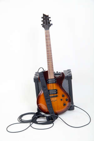 guitar and amplifier with cable, on white photo