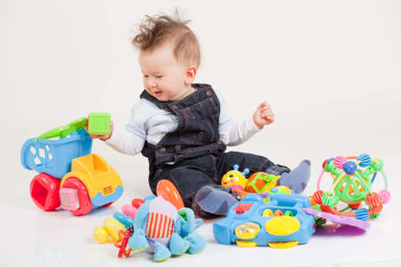happy baby playing with toys white background