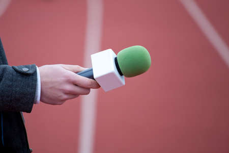 belonging to the caucasoid race: reporter holding microphone for interview Stock Photo