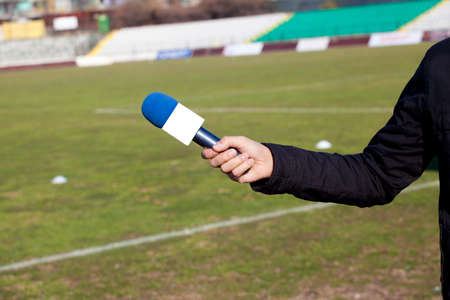 belonging to the caucasoid race: hand hold microphone for  interview during a football mach