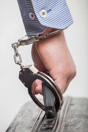 Close-up Of Person Wearing Handcuff Attached To Suitcase