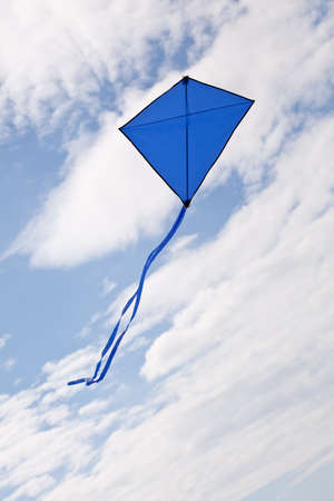 blue kite flying in a beautiful sky clouds