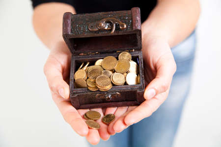 antique coins: woman hands holding old antique treasure chest with gold coins Stock Photo