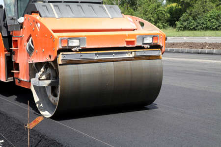 compactor: Heavy Vibration roller compactor at asphalt pavement works for road repairing Stock Photo