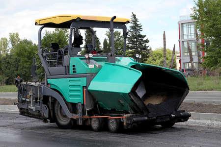asphalt paving: asphalt spreading machine. Road paving construction