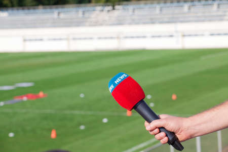 belonging to the caucasoid race: hand holding microphone for interview during a football mach Stock Photo