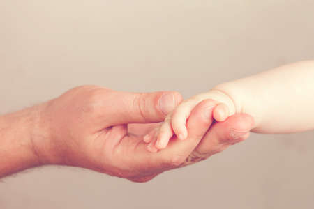 hold: Close up photo of father holding baby hand Stock Photo