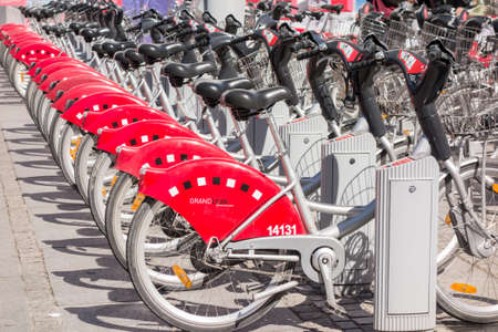 v cycle: LYON, FRANCE - on APRIL 14, 2015 - Shared bikes are lined up in the streets of Lyons, France. Velov Grand Lyon has over 340 stations and 3000 bikes throughout the Grand Lyon area.