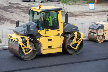 Large road-roller paving a road. Road construction Imagens - 40335490