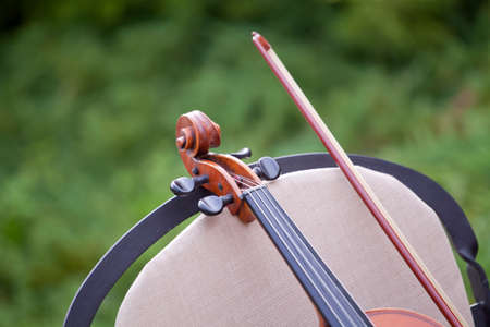 arts culture and entertainment: detail of violin and bow on a chair in the garden