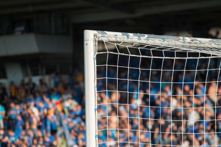 バック グラウンドでサッカーのファンとゴール ポスト 写真素材