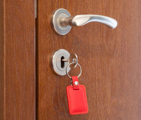 keyholder: door handle with inserted key in the keyhole with red keyholder
