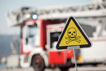 lethal: danger sign with skull and crossbones, fire truck on background