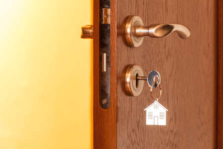 key hole: door handle with inserted key in the keyhole and house icon on it Stock Photo