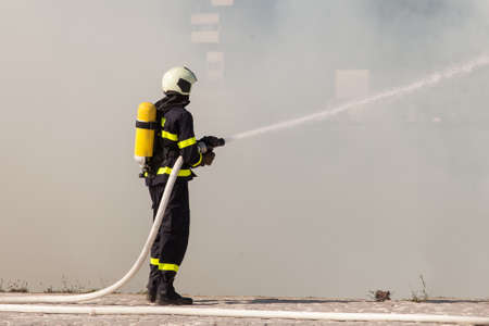 firefighter: Bombero en traje de protecci�n funciona con la manguera de agua. La lucha por un ataque de fuego