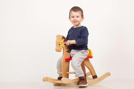 little boy on a rocking horse.