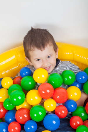 playcentre: Little smiling boy playing lying in colorful balls playground