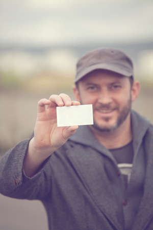casual business man: smiling casual man holding blank white card