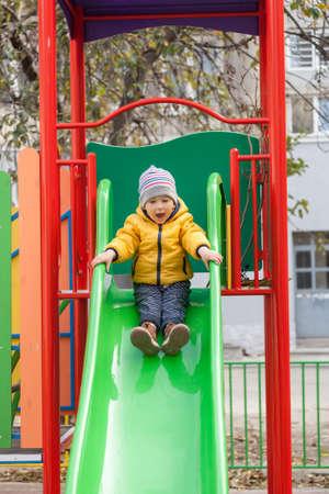 playground children: Happy boy sliding down on playground