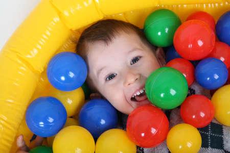 kinder: El niño pequeño sonriente que juega en las bolas de colorido parque infantil
