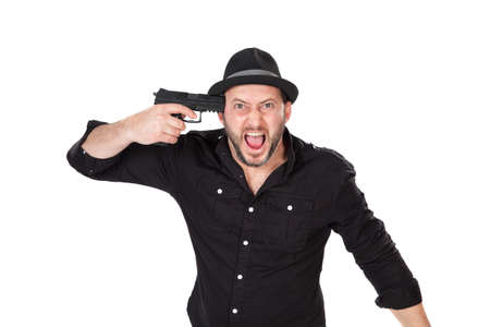 pointing gun: Angry young man pointing gun to his head Stock Photo