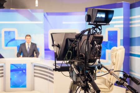 newscast: tv studio camera recording male reporter or anchorman. Live broadcasting