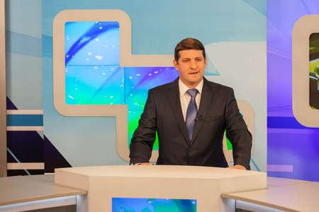 newsreader: Male anchorman in tv studio. Live broadcasting