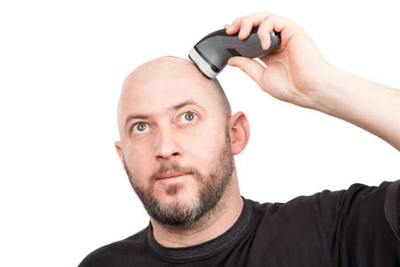 Bald man with beard shaving his head with an electric shaver