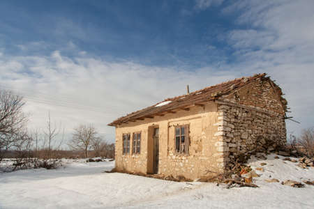 Old abandoned village house on winter