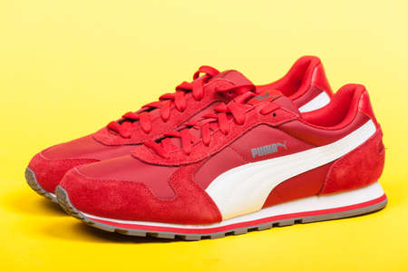 Varna , Bulgaria - JUNE 17, 2017. Red PUMA sport shoes on yellow background. Puma, a major German multinational company. Product shot Editorial