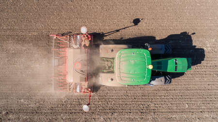 Farmer with tractor with seeder, sowing (seeding) crops at agricultural field. Top view. 写真素材