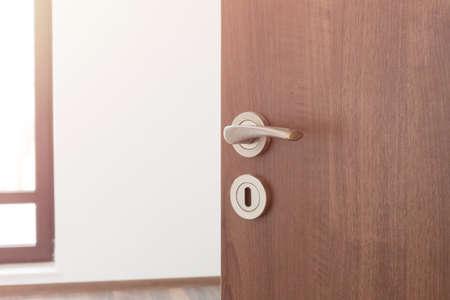 Half opened door to a ampty room. Door handle, door lock. Welcome, to new home concept