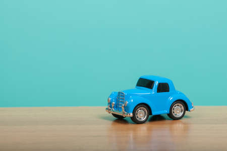 Cute blue toy car on green background. Travel concept