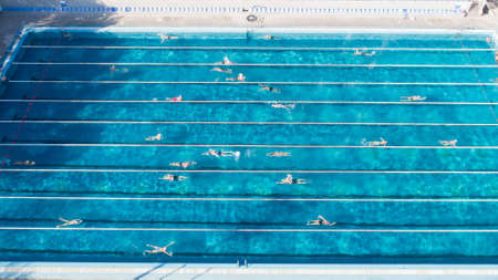 Aerial view of swimming pool with marked lanes and swimmers.