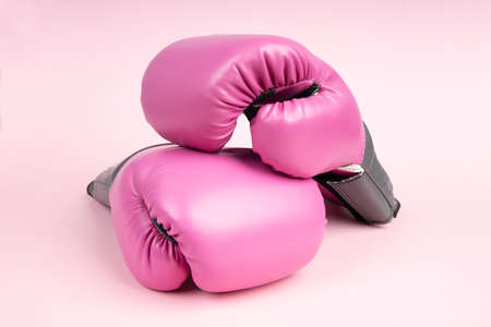 Pair of pink boxing gloves on pink background