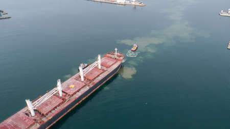 Aerial view of tug boat assisting big cargo ship. Large cargo ship enters the port escorted by tugboats.