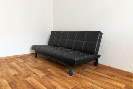 Modern black leather convertible sofa bed, wooden floor. Empty waiting room with a modern black sofa