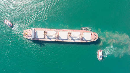 Aerial top down view of Tug boats assisting big cargo ship. Large cargo ship enters the port escorted by tugboats.